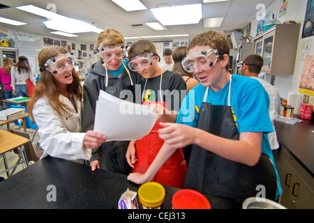 Wearing safety goggles, a high school teacher passes out an assignment sheet to her students in San Clemente, CA - Stock Photo