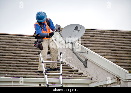 A technician installs a satellite dish on the roof of a newly purchased home in Laguna Niguel, CA - Stock Photo