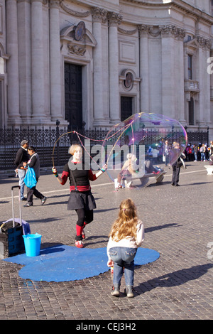 A street artist creates giant bubbles for children, in front of the Sant'Agnese in Agone basilica in Piazza Navona - Stock Photo