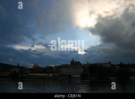 Prague Castle at dusk with the Vltava river in front. - Stock Photo