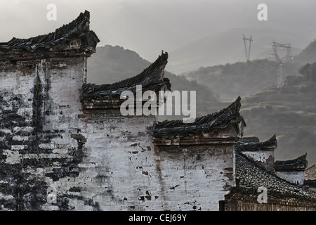 A Chinese hui style wall and roof shaped like horse heads and harmonized with black and white color, mountains in - Stock Photo