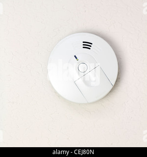 Small round battery operated device to warn residents of fire. White smoke detector on a ceiling close-up in a home - Stock Photo