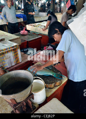 Local woman cutting fish at the market in puerto ayora on for Fresh fish market near me