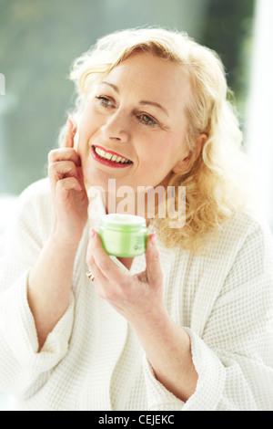 Woman applying face cream - Stock Photo