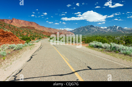 Long empty highway travels through the desert canyons of the American Southwest near Arches National Park outside - Stock Photo