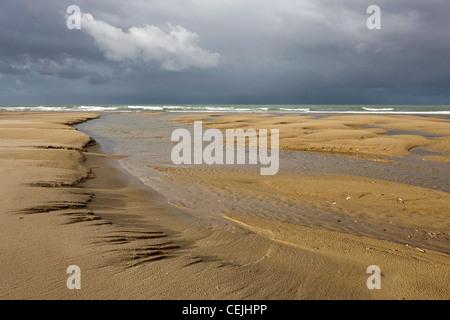 Tide pools on sand beach at low tide at Cap Blanc Nez, Pas-de-Calais, France - Stock Photo