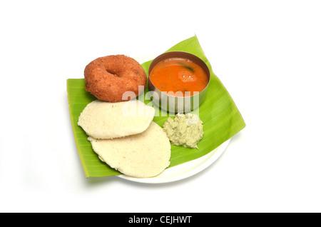 Idli, vada, sambar and chutney, south Indian breakfast served on banana leaf, isolated on white background - Stock Photo