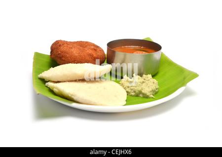 Idli, vada sambhar and chutney, south Indian dish served on Banana Leaf, isolated on white background - Stock Photo