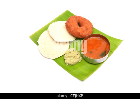 Idli, vada, sambhar and chutney, south Indian dish served on Banana Leaf isolated on white - Stock Photo
