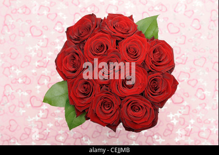 Bouquet of red roses with pink hearts in background - Stock Photo