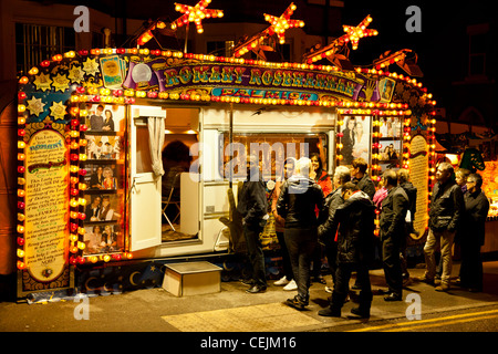 A small crowd waiting for their fortune to be told by a Romany gypsy fortune teller. Goose Fair, Nottingham, England, - Stock Photo