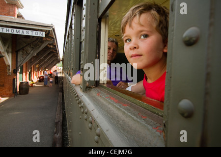 A child looking out a train window. - Stock Photo