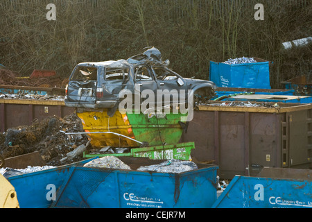 A car on the top of skips in a scrapyard. - Stock Photo