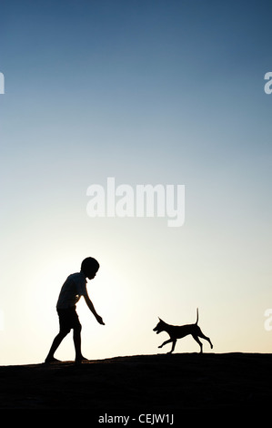 Silhouette of young Indian boy playing with his puppy. India - Stock Photo