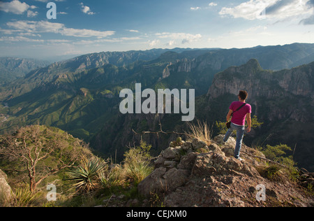 A man standing on the ridge of a cliff at the Copper Canyon in the region of Cerocahui, Chihuahua  Mexico. - Stock Photo