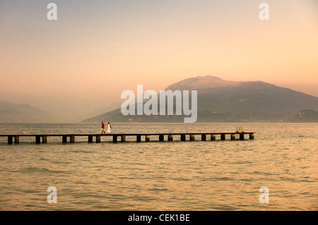 Romantic summer evening on Lake Garda, Lombardy, Italy. Couple walking on pier. Northeast from Sirmione to Monte - Stock Photo