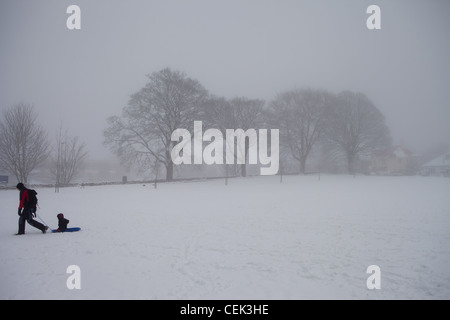 A father pulling his son on a sledge over a snow covered field - Stock Photo