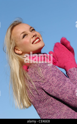 Semi profile of female long blonde hair brown tones of make up wearing purple jumper bright pink scarf and mittens - Stock Photo