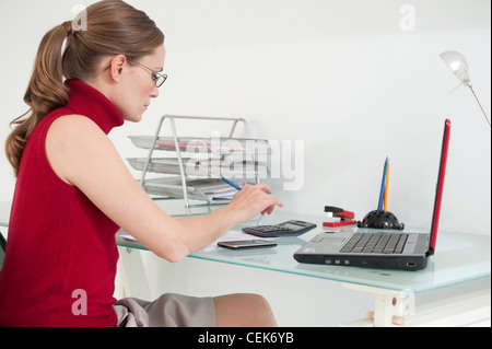 Female fair hair tied into ponytail, wearing a red sleeveless polo neck top, glasses and beige skirt, sitting by - Stock Photo