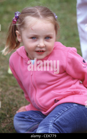 MFemale child blonde hair off face in bunches wearing pink zip up hooded top blue jeans sitting on grass looking - Stock Photo