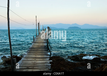 Ko Wai island in Thailand, Gulf of Thailand at dusk, wooden pier on turquoise water and islands on the horizon - Stock Photo