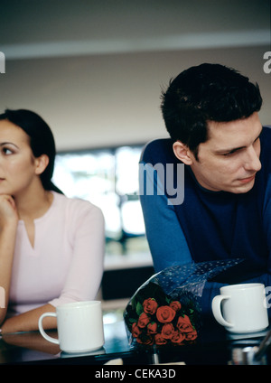 MMale brown hair wearing blue and black top leaning on table white mugs and bunch of red roses looking to one side - Stock Photo