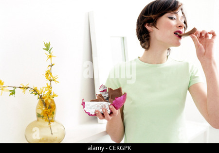 Female standing in living room holding up a half unwrapped foil wrapped chocolate Easter egg in one hand, and eating - Stock Photo