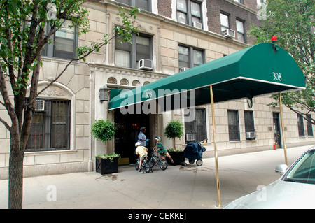 Upper East Side luxury apartment building in New York on East 79th  Street seen on June. Doorman in the entrance of an Upper East Side apartment building
