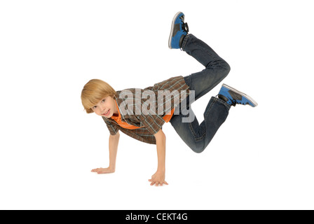 Eleven year old boy wearing earbuds, listening to mp3 player and dancing on the floor. - Stock Photo