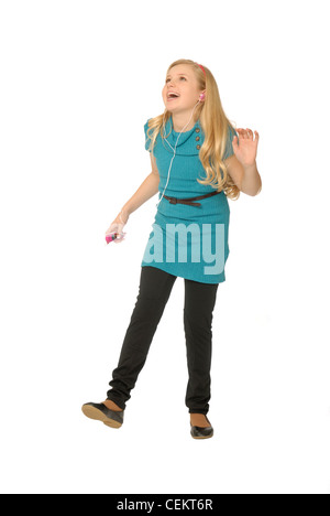 Ten year old girl wearing earbuds, listening to mp3 player and dancing. - Stock Photo