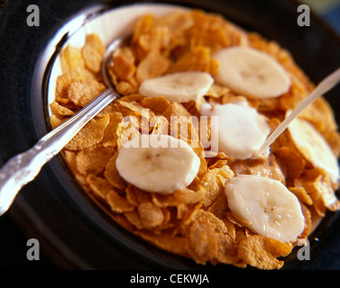 A bowl of cornflakes topped with sliced banana, with milk being poured onto the cornflakes - Stock Photo