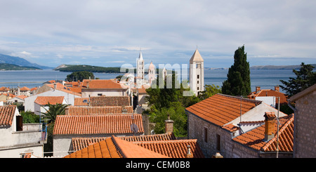 Rab, Primorje-Gorski Kotar, Croatia. View over tiled rooftops to the Adriatic, ancient bell-towers prominent. - Stock Photo