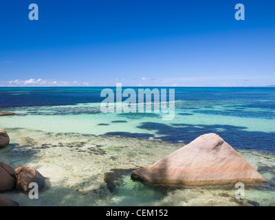 Anse Bois de Rose, Praslin, Seychelles. View across the clear waters of the Indian Ocean, granite boulders in foreground. - Stock Photo