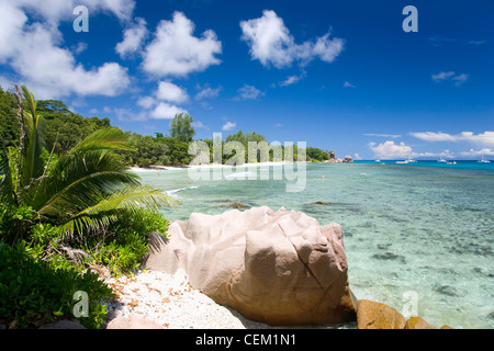 Anse Sévère, La Digue, Seychelles. View across the bay, granite boulders in foreground. - Stock Photo