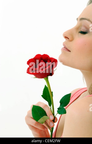 Female wearing a pink vest, holding a single red rose with one hand, unsmiling, breathing in the smell of rose - Stock Photo