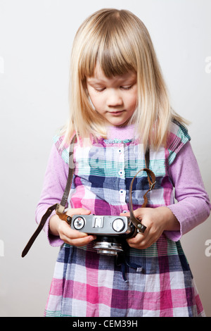 Little girl with a vintage camera. Studio shot. - Stock Photo