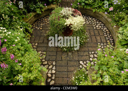 Modern Victorian Garden Detail image of paved garden path raised borders and various small succulents in the bowl - Stock Photo