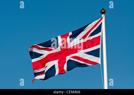 A union jack flag flying against a clear bright blue sky. - Stock Photo