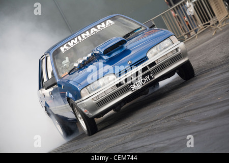 Australian Holden Commodore drag race racing car performing a burnout to heat up the rear tires. - Stock Photo