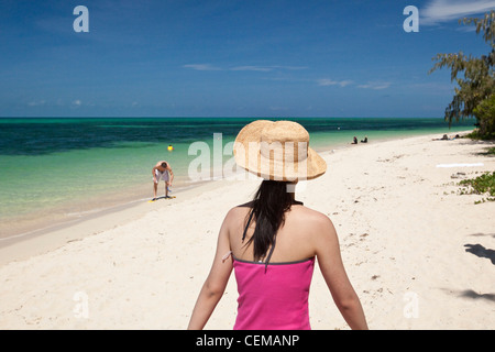 Woman walking along beach on Green Island - a coral cay off the coast of Cairns. Great Barrier Reef, Queensland, - Stock Photo