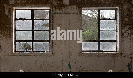 Broken windows inside a disused factory in Yorkshire. - Stock Photo