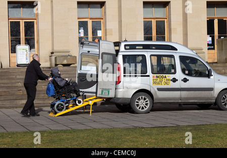 Taxi driver assisting passenger in wheelchair to leave using ramp. Newcastle north east England UK - Stock Photo