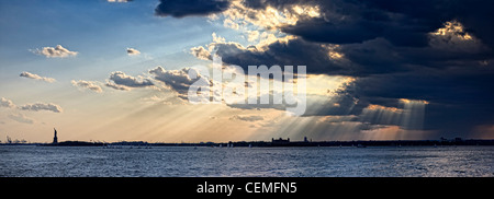 Golden rays of Sun piercing through dark clouds, and shining on Statue of Liberty and Ellis Island of New York Harbor, USA