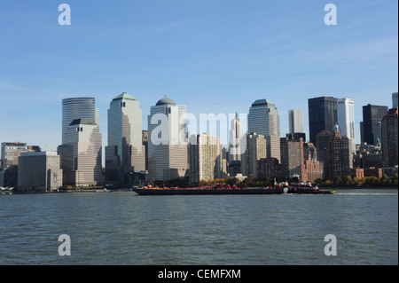Blue sky view, from Hudson River, bulk-carrier barge moving front World Financial Centre skyscrapers, Lower Manhattan, - Stock Photo