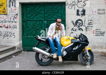 Young man on motorbike in front of revolutionary graffiti in Zamalek Cairo Egypt - Stock Photo