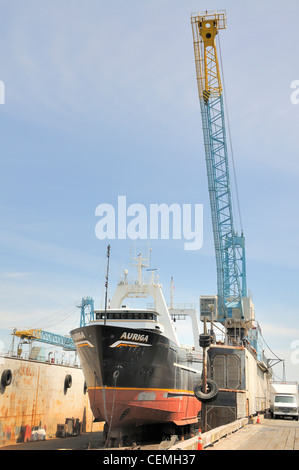 A large ship in dry dock, with a crane attached to dry dock in image. - Stock Photo