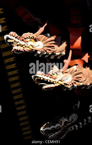 Carved wooden dragons emerging from the darkness in a Japanese Temple. - Stock Photo