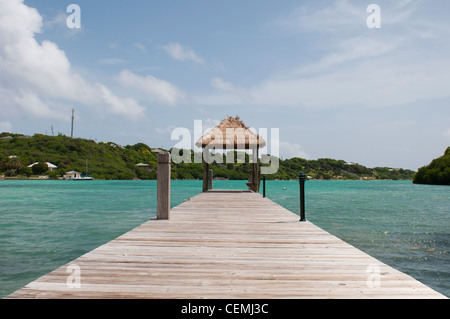 tropical wooden jetty with hut over sea in Long Bay, Antigua - Stock Photo