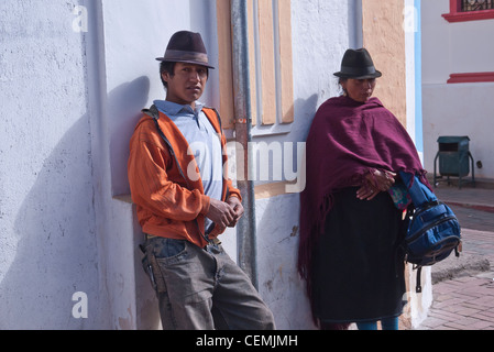 Two Ecuadorians, a young adult male and an older adult female, wait for a bus by the side of a building in Pujili, - Stock Photo