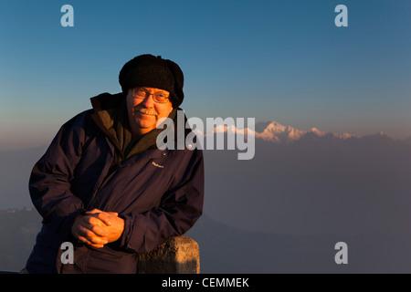 India, West Bengal, Darjeeling, Tiger Hill, western man tourist posing in front of Kangchenjunga at dawn - Stock Photo